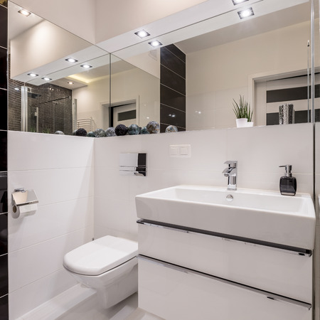 White bathroom with mirror wall, cabinet basin, toilet and led lighting Stock Photo