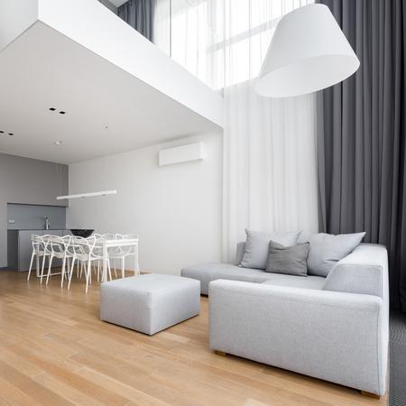 Appartamento moderno arredato con divano ad angolo, grande lampada e soppalco