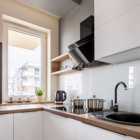Small kitchen with white furniture, wooden worktop and window Banco de Imagens