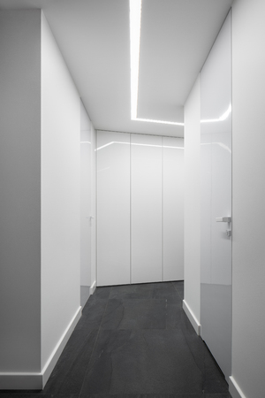 White home interior with high, white and shiny closet and decorative led lighting on the ceiling