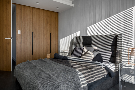Sunlight in modern bedroom with wooden wardrobe and decorative wallpaper Banque d'images