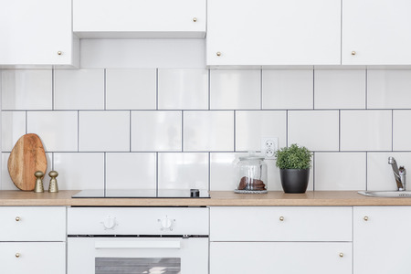 Scandinavian style kitchen with white cabinets and wooden countertop Banco de Imagens