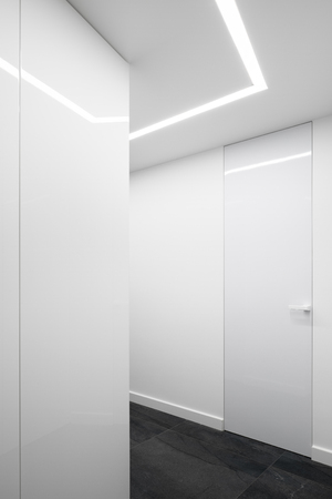 White interior with gray floor tiles and decorative led light on ceiling Stock Photo