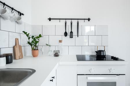 Moderne Küche mit weißen Wandfliesen und funktionalen schwarzen Kleiderbügeln