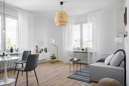 Gemütlicher Wohnungsinnenraum mit Sofa, rundem Tisch und Stühlen