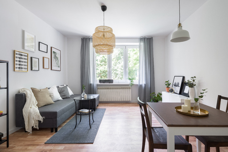 Scandinavian living room with wooden dining table and decorative bamboo lamp
