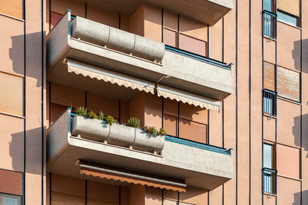 Close-up on stylish balconies with flower pots and awnings
