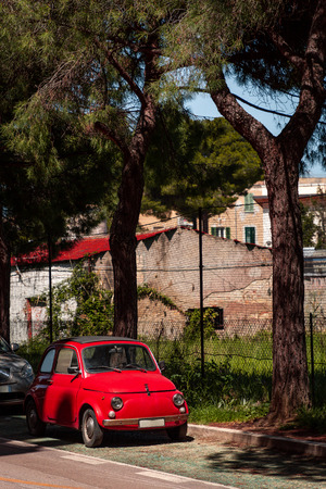 Retro and italian style red car parked on green avenue