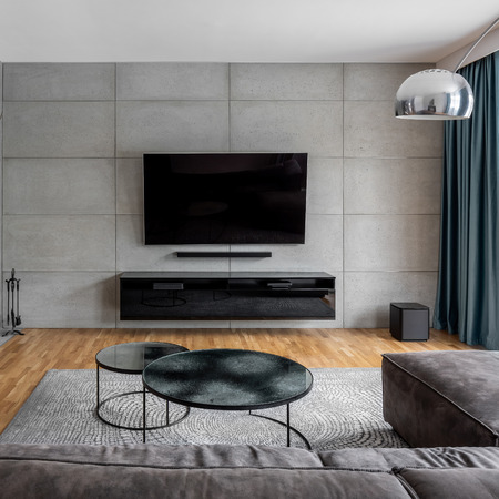 Living room with cement wall and wall mounted tv