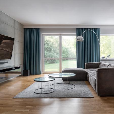 Modernes Wohnzimmer mit großen Fenstern, Betonwand und Ecksofa Standard-Bild