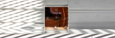 New design golden glass clock standing on a white stylish dresser, panorama 免版税图像