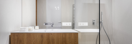 Panorama of bathroom with shower, big mirror and wooden basin cabinet Imagens