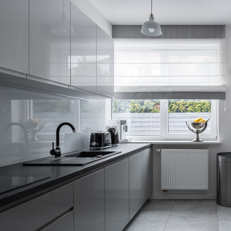 Narrow kitchen with big window and stylish, contemporary and gray furniture