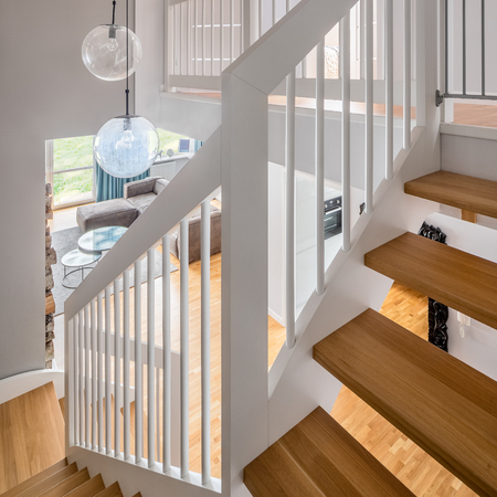 Home interior with classic wooden stairs and white balustrade