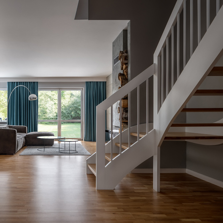 Cozy home interior with wooden stairs and open living room Archivio Fotografico