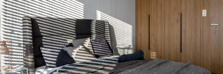 Panorama of gray bedroom with double bed and wooden wardrobe and shadow from window blinds