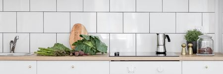 Simple kitchen with white tiles and cupboards and wooden countertop, panorama