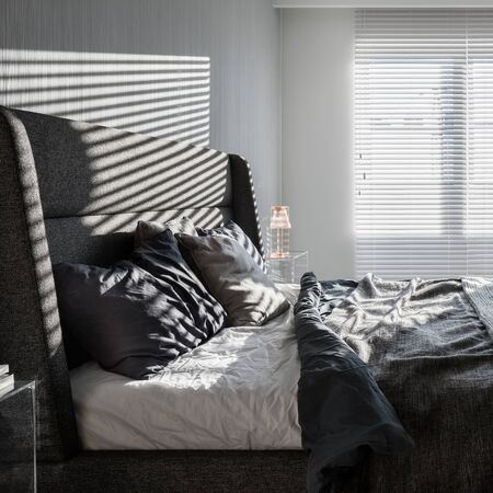 Sunny, gray bedroom with double bed and window blinds Banque d'images