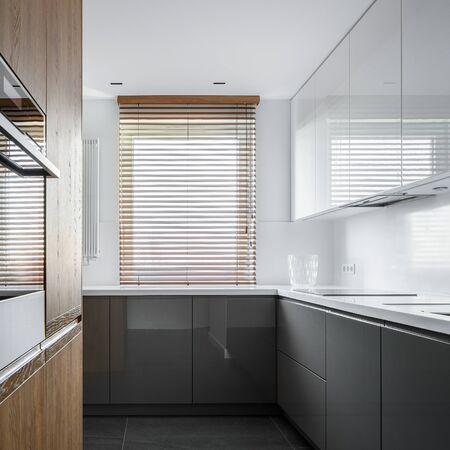 Cocina estrecha con mueble gris y blanco y detalles de madera. Foto de archivo