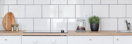 Panorama of kitchen with wooden worktop and white tiles on backsplash