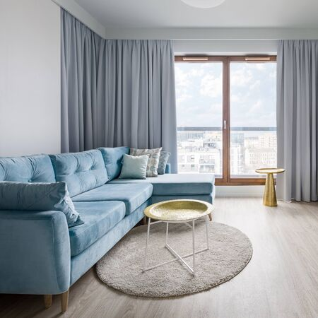 Contemporary living room in gray, blue and white with big sofa and window