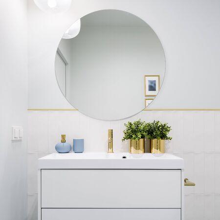 Baño luminoso con espejo redondo, mueble blanco con cajones y decoraciones azules y doradas.