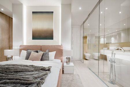 Camera da letto principale di lusso con letto matrimoniale accanto all'elegante bagno dietro la parete di vetro Archivio Fotografico