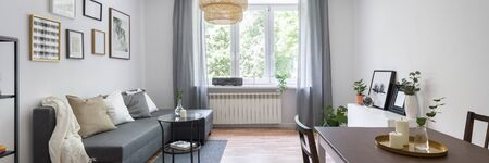 Stylish and small living room in gray and white with big window, panorama Stock fotó