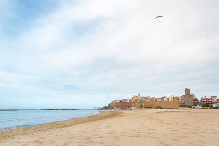 View of Termoli city in Italy with wide beach and calm sea and paraglider flying above