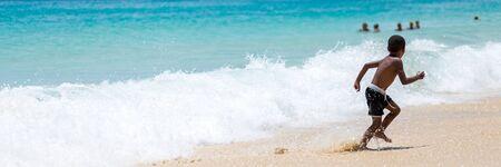 Panorama eines Jungen, der vor einer großen Ozeanwelle am Strand wegläuft Standard-Bild