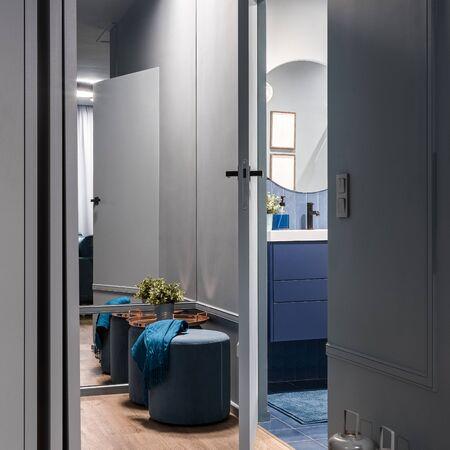 Interno del corridoio in grigio con grande parete a specchio e porta del bagno aperta