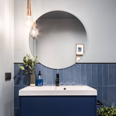 Designed bathroom with stylish blue cabinet, blue wall tiles and big round mirror Stock fotó