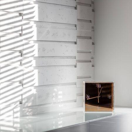 Golden glass clock standing on a white sideboard in a modern interior 免版税图像