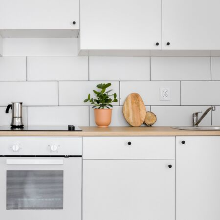Simple kitchen with white tiles, wooden worktop and induction hob