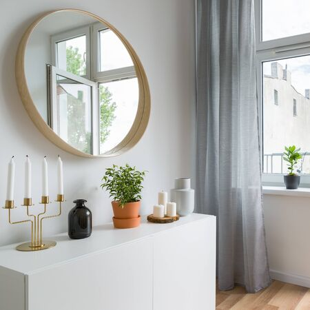 Bright home interior in scandinavian style with simple cabinet and round mirror
