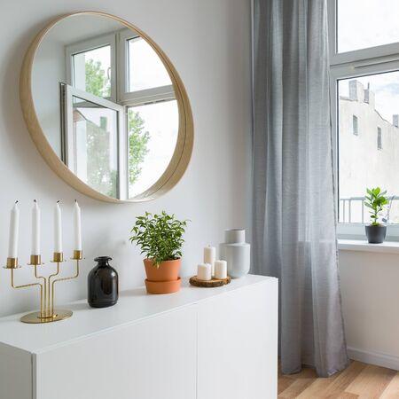 Helles Wohnambiente im skandinavischen Stil mit schlichtem Schrank und rundem Spiegel