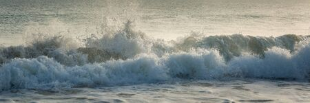 Panorama of amazing big waves on blue ocean during sunset