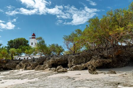 Lighthouse on rock shore by the Indian Ocean at Zanzibar island