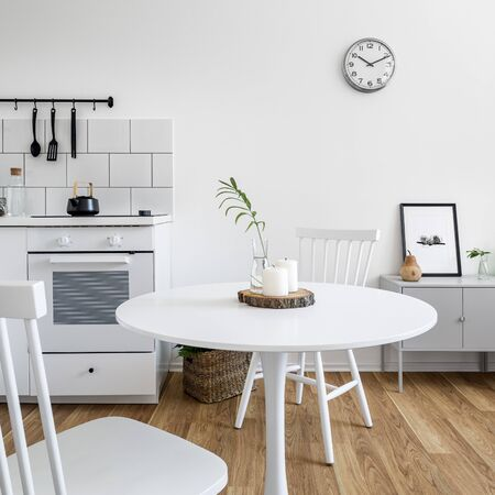 Kitchenette with white, round, dining table and two white chairs