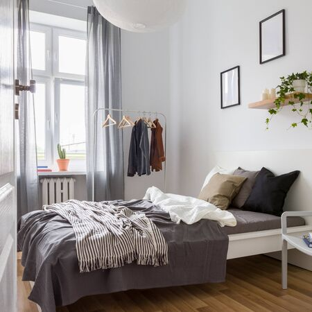Simple bedroom in gray and white with double bed, clothes rack and wall decoration Stockfoto