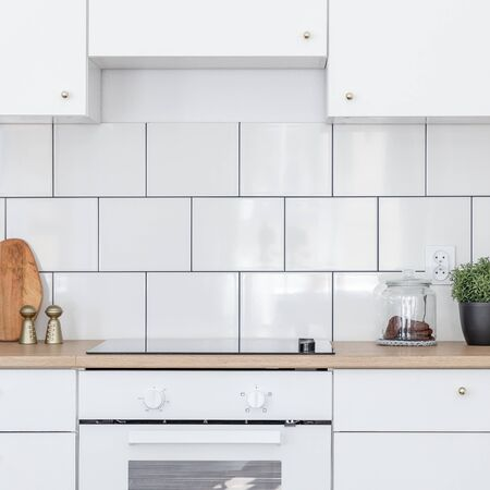 Contemporary kitchen with white tiles, wooden worktop and induction hob Stock Photo