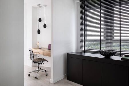 Stylish and smart home office with wooden desk in recessed wall niche