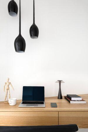 Klein houten bureau met computer, boeken en decoraties in thuiskantoor Stockfoto
