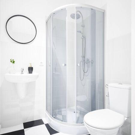 Baño de nuevo diseño con ducha e inodoro y suelo de ajedrez.