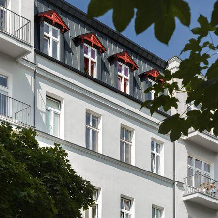 Exterior view of modern, white townhouse among trees Standard-Bild - 129442948