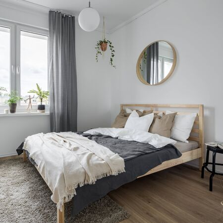Bedroom interior with wooden bed, gray window curtains and mirror Standard-Bild - 129442947