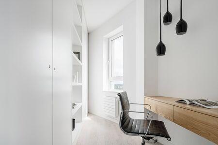 Corner home office in white with wooden desk and big wardrobe Archivio Fotografico