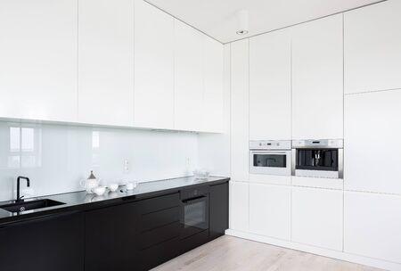 Modernes schwarz-weißes Kücheninterieur mit eingebauter Küchenausstattung