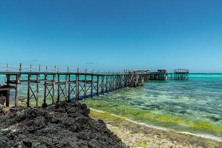 Long and old wooden pier over blue Indian Ocean, Zanzibar island Archivio Fotografico