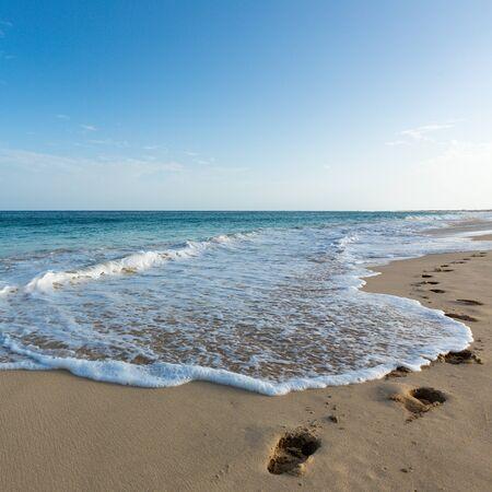 Schritte an einem Strand, der von einer wunderschönen blauen Ozeanwelle weggespült wird